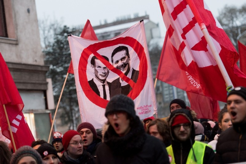 Protesters holding a sign with crossed out faces of Austria's Chancellor Sebastian Kurz of OeVP and Vice-Chancellor Heinz-Christian Strache of FPOe during a protest against the coalition government in Vienna, Austria, Dec. 15, 2018. (EPA Photo)