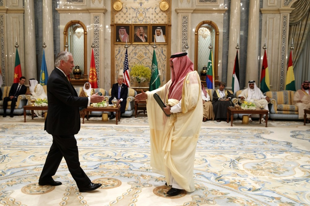 President Trump (C, rear) looks on as U.S. Secretary of State Tillerson (L) and then Saudi Crown Prince Muhammad bin Nayef (R) exchange a handshake during a meeting of the GCC in Riyadh, Saudi Arabia, May 21.