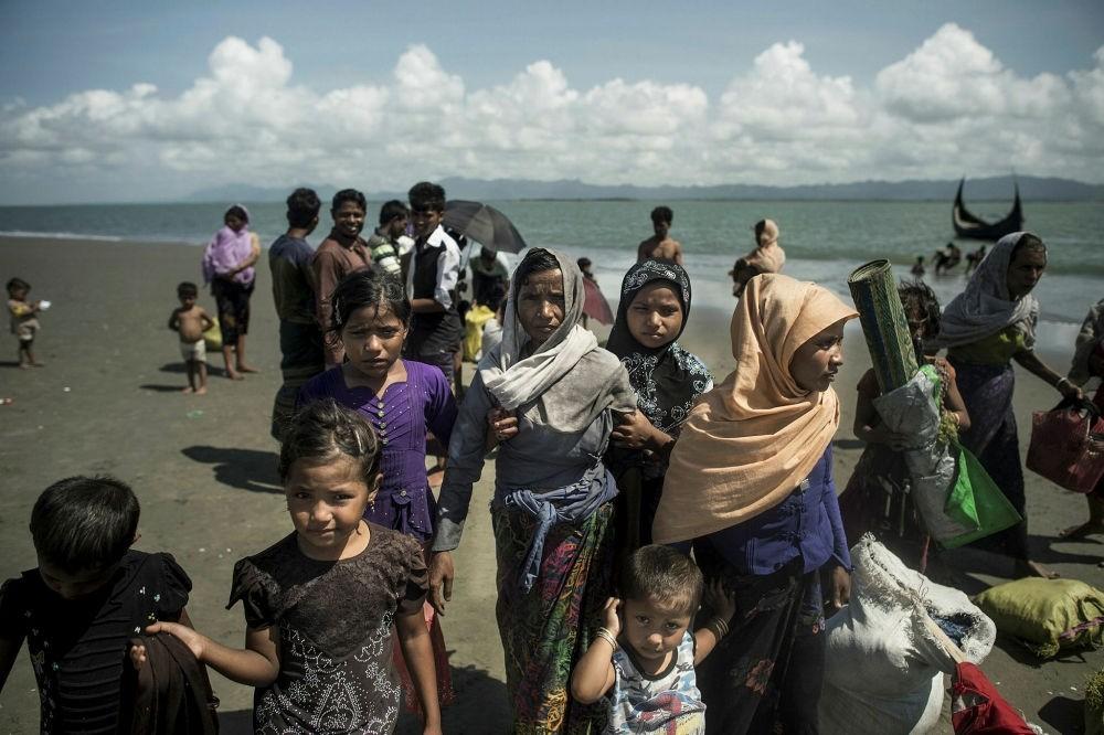Rohingya Muslim refugees walk on the Bangladeshi shoreline of the Naf River after crossing the border from Myanmar in Teknaf on Sept. 30.