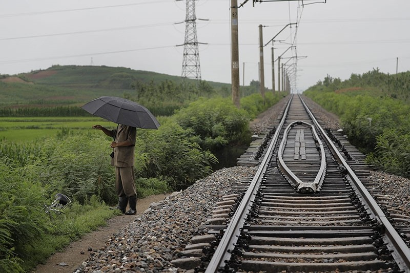 In this Friday, July 21, 2017, photo, a man stands near the pathway leading to where an unexploded bomb was found near the railway which runs through Hamhung from Pyongyang to the northeastern port of Chongjin. (AP Photo)
