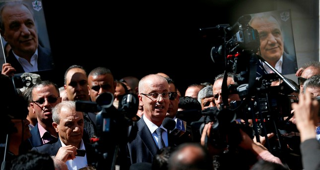 Palestinian Prime Minister Rami Hamdallah (C) addresses the media upon his arrival in the West Bank town of Ramallah following his return from the Gaza Strip where an explosion targeted his convoy, March 13.