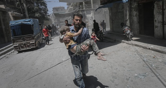 A man flees while carrying a child in northwest Syria's Idlib during Assad regime's air strikes, May 27, 2019. AA Photo