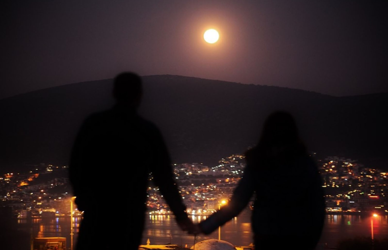 A couple holds hands while watching supermoon at the historical Değirmenler Hill in southern Muğla province's Bodrum (IHA Photo)