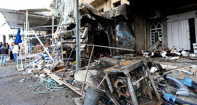 Iraqi men inspect the aftermath of a car bomb attack in the Amil district, west of Baghdad, Iraq, 21 March 2017. (EPA Photo)