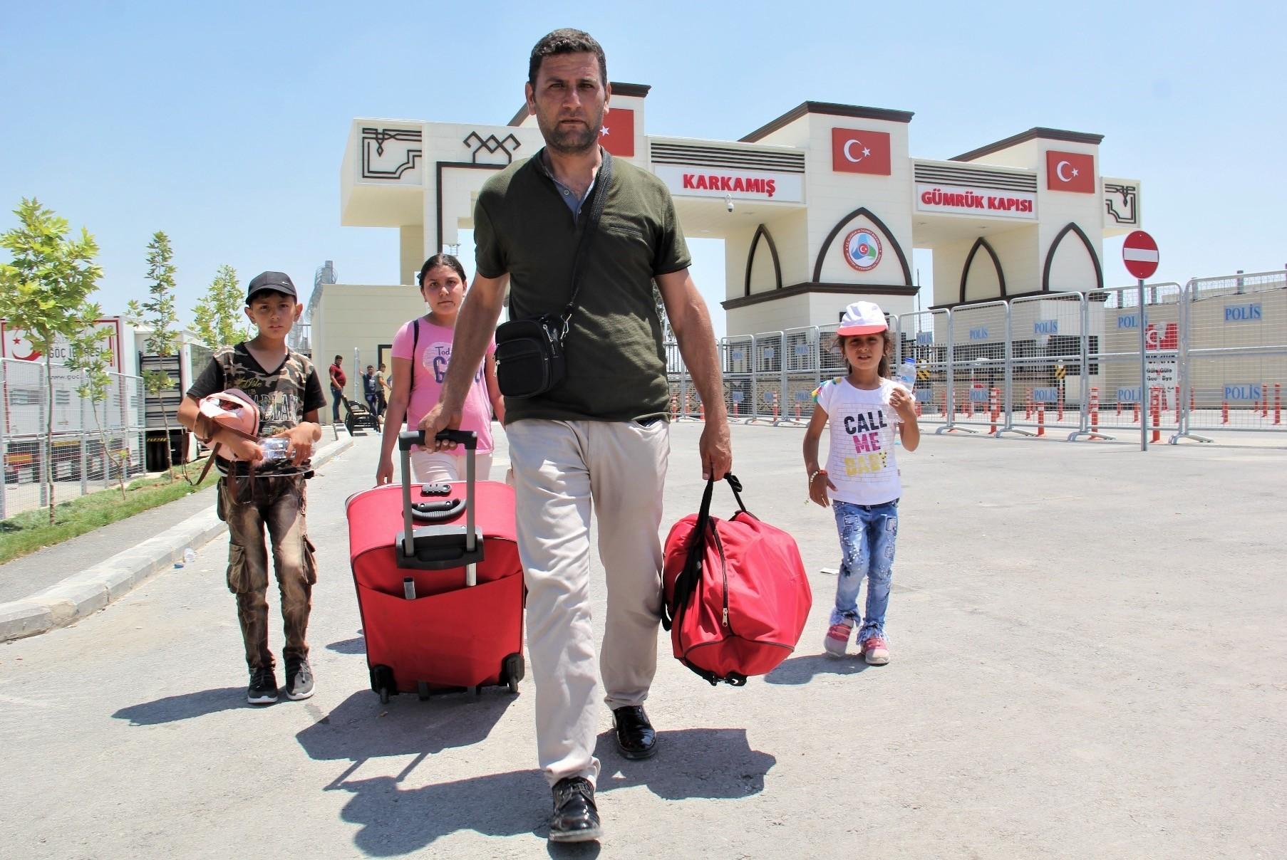 A Syrian man and three children cross into Turkey from the Karkamu0131u015f crossing.
