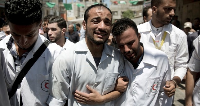 Palestinian paramedics mourn during the funeral of their colleague, Abdullah al-Qutati, who was shot and killed during the Friday's protest at the Gaza Strip's border with Israel, in town of Rafah, southern Gaza Strip, Aug.11, 2018. (AP Photo)