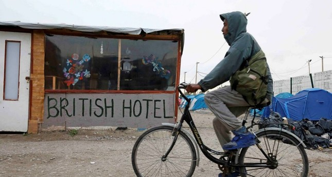 A migrant rides a bicycle in the northern area of the camp called the Jungle in Calais, France, Sept. 26, 2016.