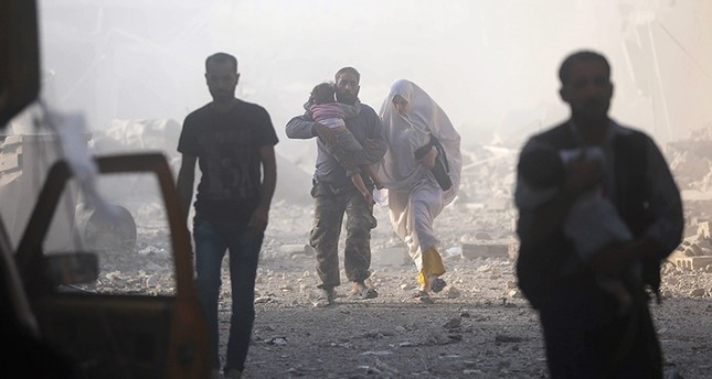 Syrians emerge from a dust cloud following a reported airstrike on Kafr Batna, in opposition-held eastern Ghouta, on the outskirts of Damascus, on Sept. 30, 2016 (AFP Photo)