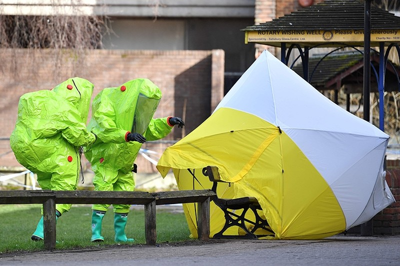 In this file photo taken on March 8, 2018 members of the emergency services in green biohazard encapsulated suits re-affix the tent over the bench where Russian spy Sergei Skripal and his daughter Yulia were found in critical condition. (AFP Photo)