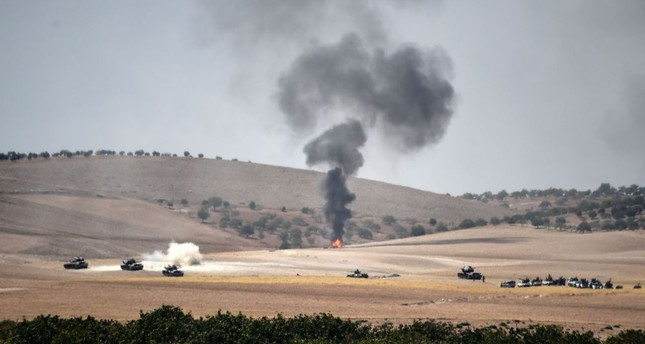 Turkish army tanks and alleged Syrian moderate fighter trucks positioned 2 kilometres west from Jarablus the Syrian town on the border with Turkey, preparing to move position, to Karkamış in Turkey's southeastern Gaziantep province, Aug. 24.
