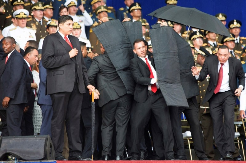 In this photo released by China's Xinhua News Agency, security personnel surround Venezuela's President Nicolas Maduro during an incident as he was giving a speech in Caracas, Venezuela, Saturday, Aug. 4, 2018. (Xinhua via AP)
