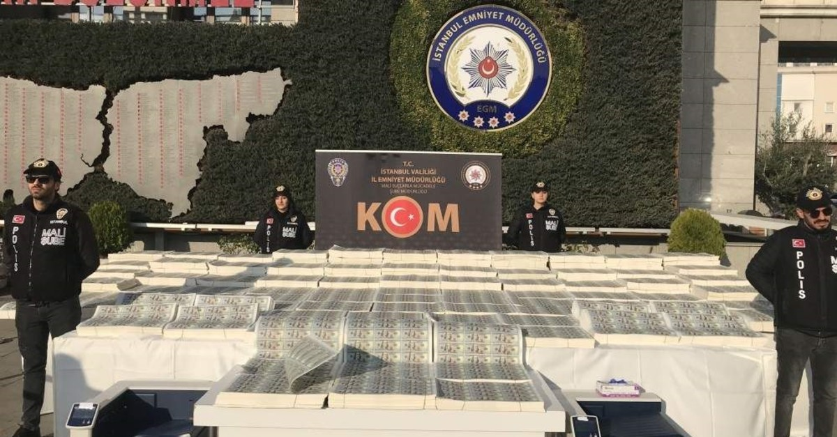 Police officers stand next to seized counterfeit U.S. dollar bills displayed in the courtyard of Istanbul Security Directorate, Jan. 15, 2019. (AA Photo)
