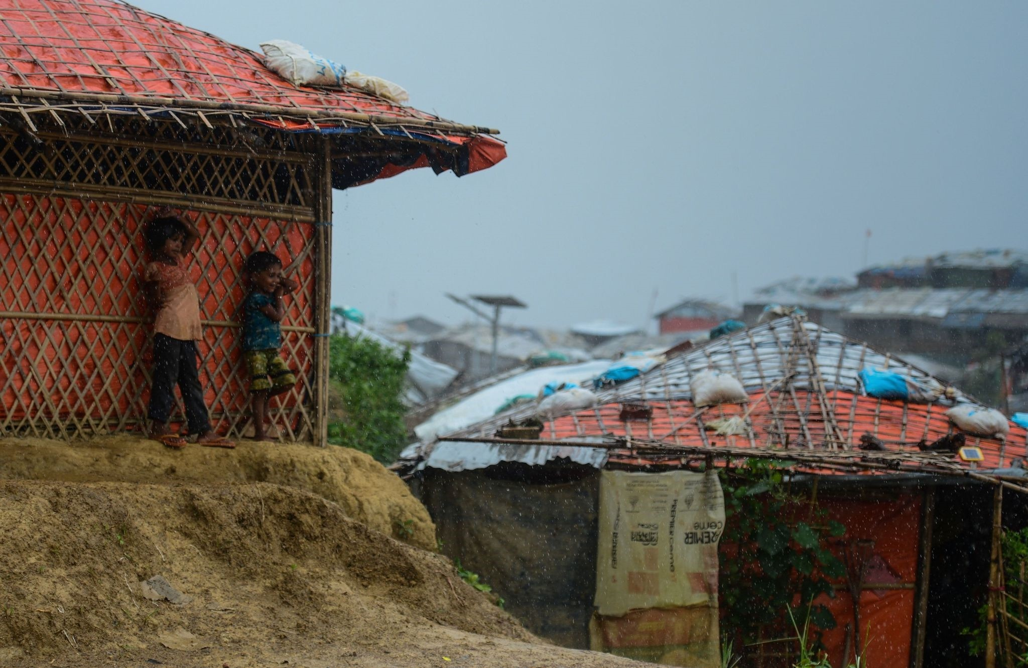 Rohingya refugee children take shelter during a rain storm at Balukhali refugee camp, Ukhia, July 21.