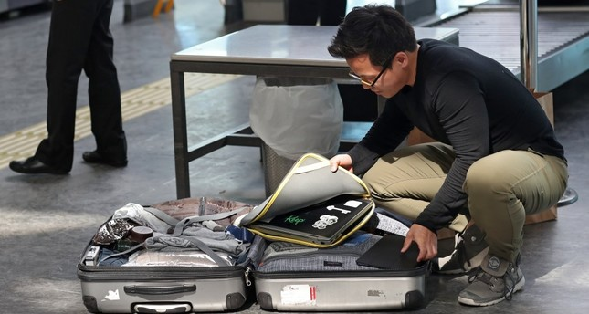 Passengers open their luggage and show their electronic equipment at a security point at Atatürk Airport in Istanbul.