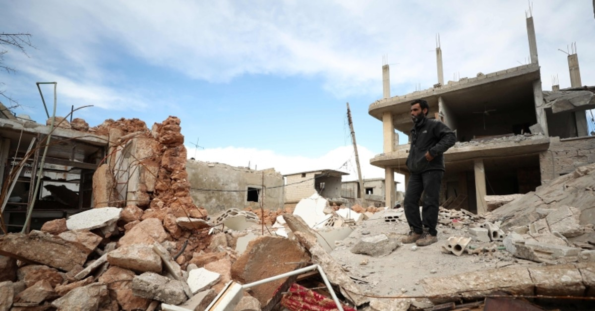 Wael, the father of four, stands amidst the rubble of a destroyed building in the town of Saraqeb, in in Syria's northwestern Idlib province on January 31, 2020. (AFP Photo)
