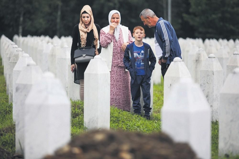 People look at a fresh grave prepared on the Potocari Memorial Center in Srebrenica, Bosnia and Herzegovina, July 11.