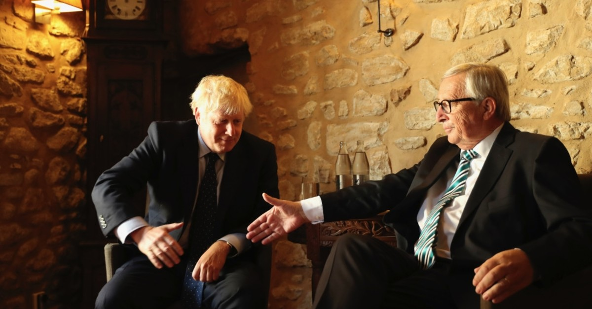 European Commission President Jean-Claude Juncker (R) reaches out to shake hands with British Prime Minister Boris Johnson prior to a meeting at a restaurant in Luxembourg, Sept. 16, 2019.