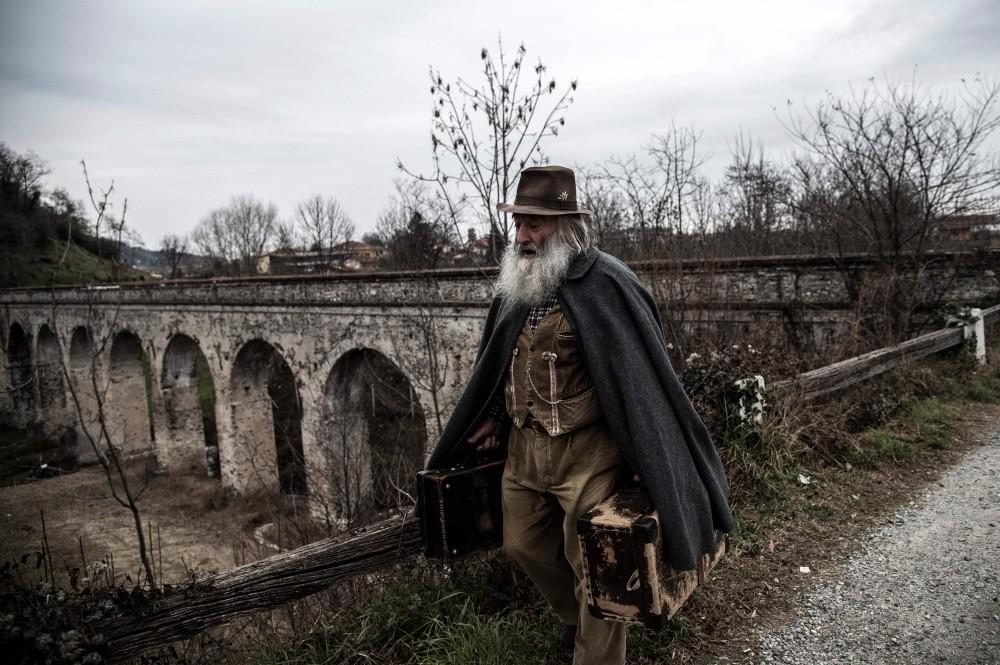 Mario Collino walks on a path toward the village of Busca.
