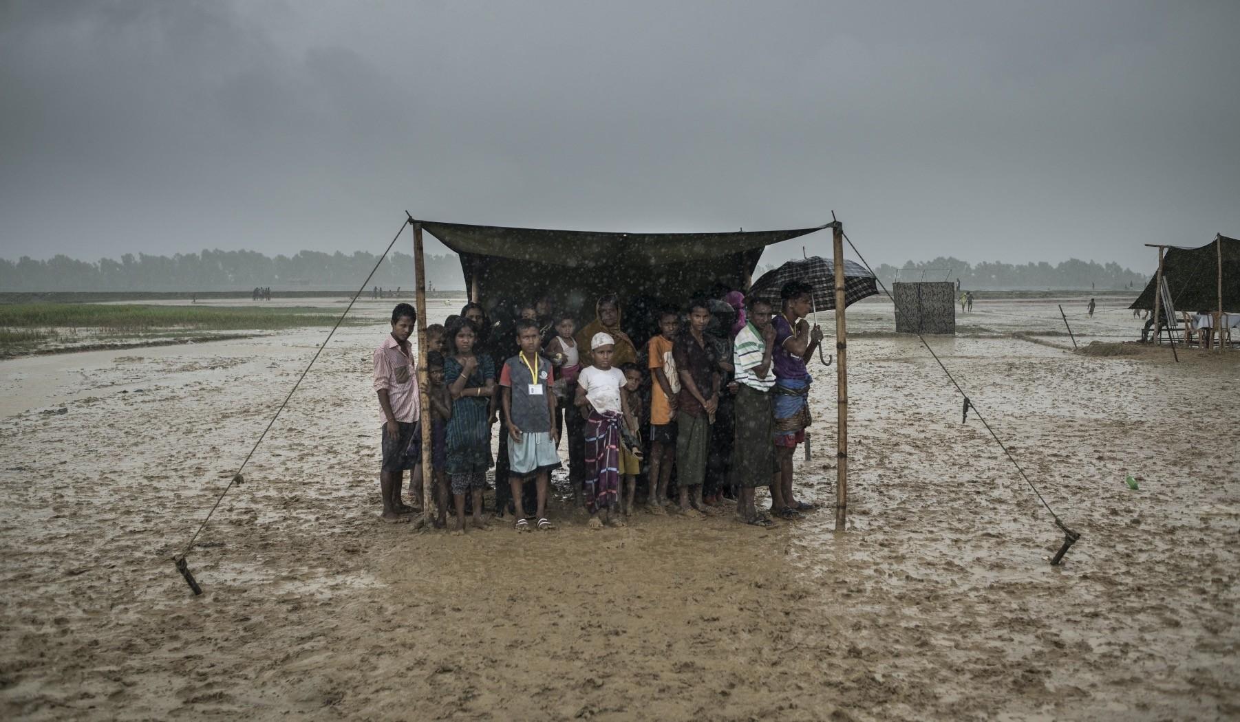 Rohingya Muslim refugees take shelter from the rain during a food distribution, Nayapara refugee camp, Ukhia, Bangladesh, Oct. 6, 2017.