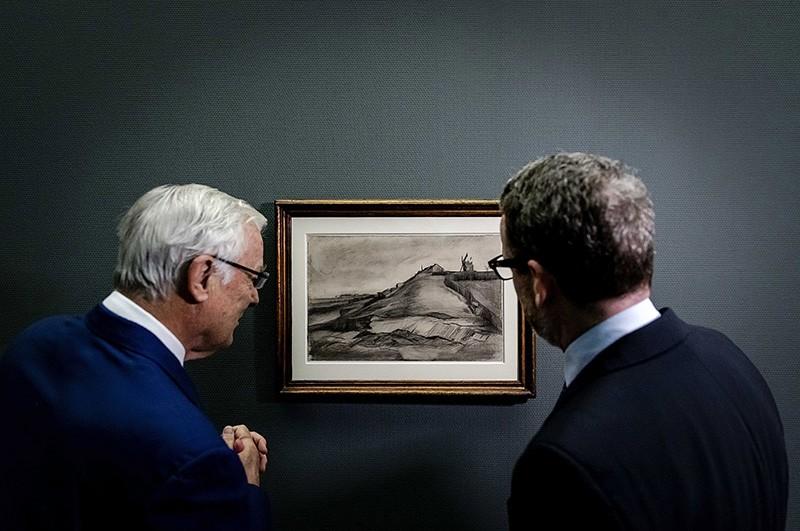 Dutch businessman John Fentener van Vlissingen (L) and Axel Ruger (R), the director of the Van Gogh Museum, look at a new drawing of Van Gogh at the Singer Museum in Laren, the Netherlands, 16 Jan. 2018. (EPA Photo)