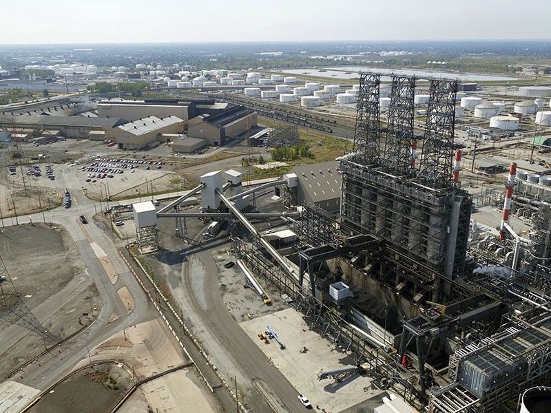 In this Sept. 21, 2017 file photo, petroleum coke, the grainy black byproduct of refining Canadian tar sands oil, is visible at the BP Whiting refinery in East Chicago, Ind. (DroneBase via AP)