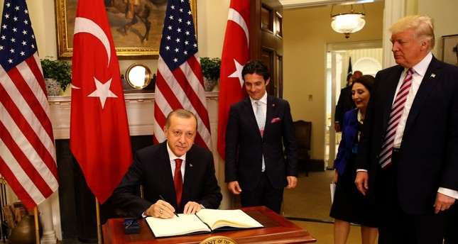 President Erdoğan signs on the U.S. guest book in the Oval office of the White House during his first visit to Washington since Donald Trump became the president, May 16.