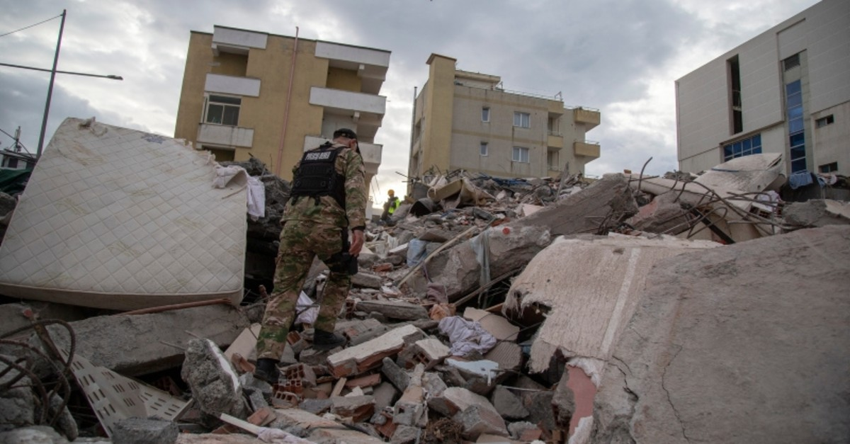 A member of the Albanian special police forces walks on a collapsed building in Durres, western Albania, Thursday, Nov. 28, 2019. (AP Photo)