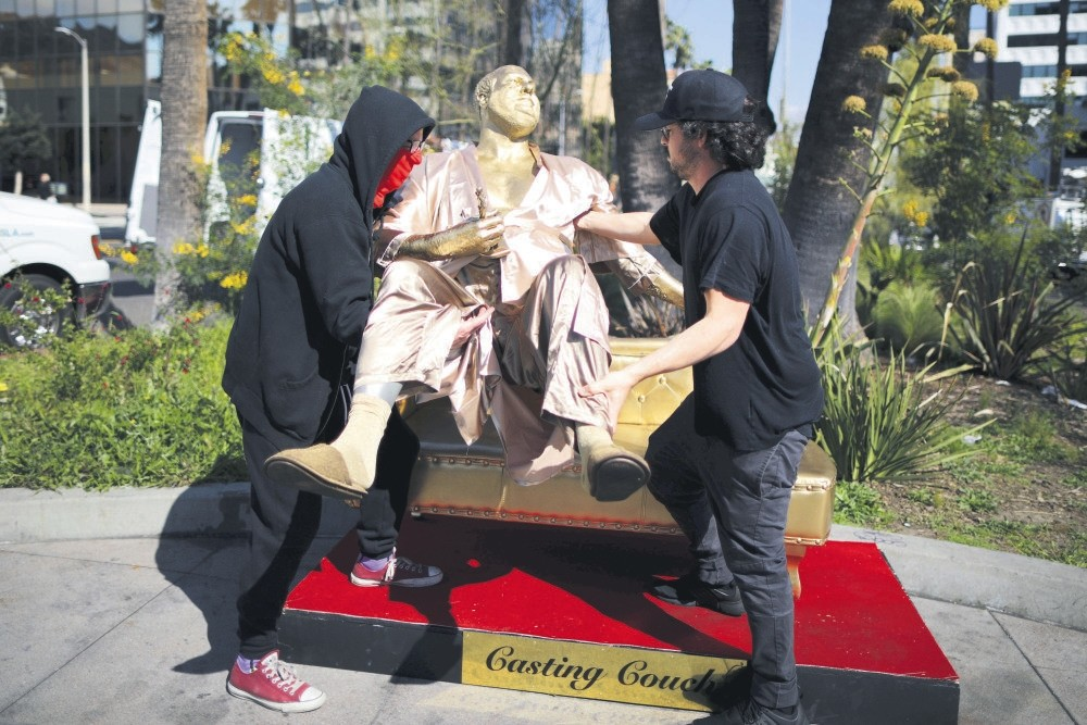 Artist Plastic Jesus (L) picks up his statue of Harvey Weinstein on a casting couch on Hollywood Boulevard near the Dolby Theatre during preparations for the Oscars in Hollywood, Los Angeles.