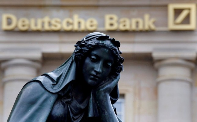 A statue is seen next to the logo of Germany's Deutsche Bank in Frankfurt, Germany, January 26, 2016.