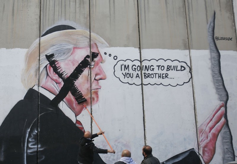A Palestinian paints over a mural of President Trump during a protest in Bethlehem, the West Bank, Dec. 7, 2017. (AP Photo)