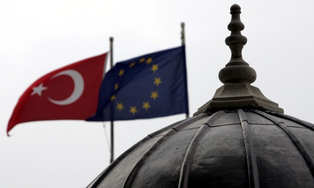 The Turkish and European Union flags waving side by side in Istanbul, where the minarets and domes of mosques and churches dominate the cityu2019s silhouette.
