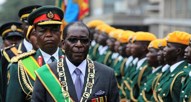 Zimbabwe's former President Robert Mugabe inspects the guard of honour during the official opening of the second session of the seventh parliament of Zimbabwe in Harare (AP Photo)