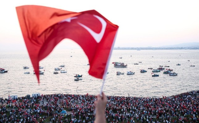 A person waves a Turkish flag during a rally at Gündoğdu Square in İzmir to protest against the failed July 15 failed coup attempt. (AFP Photo)