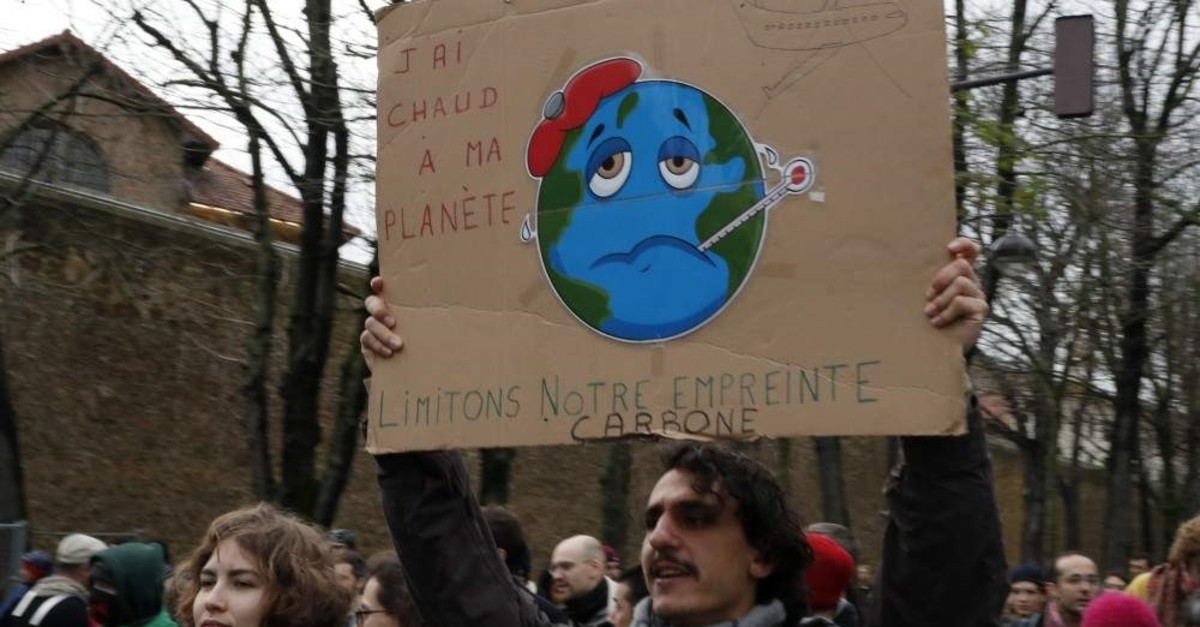 Protestors holding a cardboard reading ,I am hot for my planet, limit the carbon print, take part of a climate change protest march in Paris, Dec. 8, 2019. (AP)