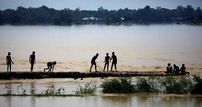 Villagers stand on a higher ground as they swim on the flood water in Saptari District, Nepal August 14, 20017. (Reuters Photo)