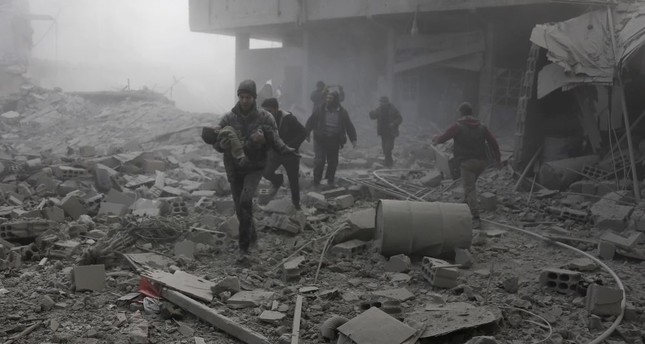 A man carries a child after digging him out of the rubble following an airstrike on Hamouria, in opposition-held eastern Ghouta, near Damascus, Jan. 9.