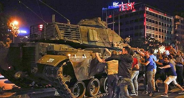 People try to stop a tank commanded by putschists in Ankara on July 15, 2016.