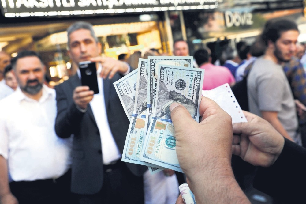 A businessman holding U.S. dollars poses for his friend in front of a currency exchange office in response to President Erdou011fan's call on Turks to sell their dollar savings to support the Turkish lira, Ankara, Aug.14.