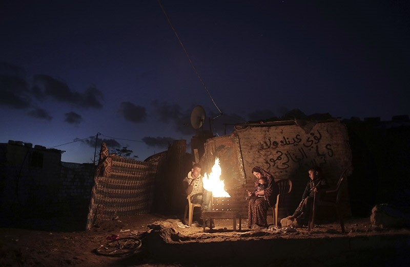 In this Sunday, Jan. 15, 2017 file photo, a Palestinian family warm themselves up with a fire outside their makeshift house during a power cut in a poor neighborhood in town of Khan Younis in the southern Gaza Strip. (AP Photo)