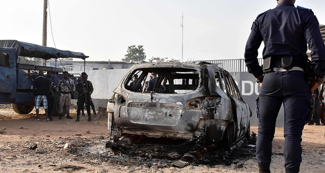 A gendarme stands in front of the wreckage of a burnt car, on Jan. 10, 2018 in front of the CCDO elite military unit center, a day after gunshots and heavy weapons fire erupted between rival factions within Ivory Coast's army. (Reuters Photo)