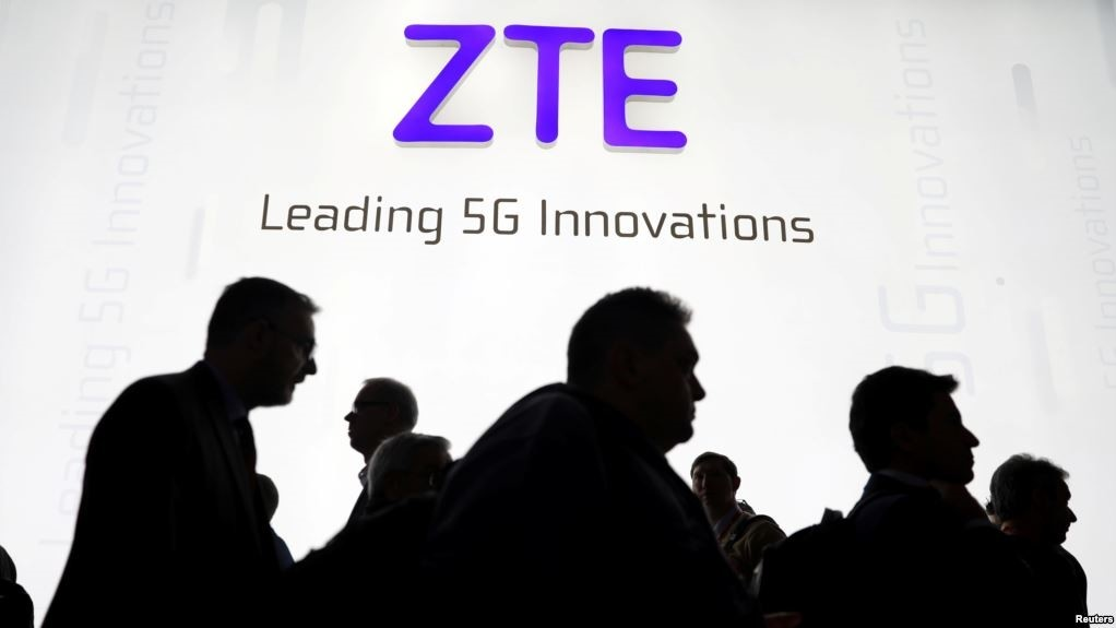 Visitors pass in front of the Chinese telecoms equipment group ZTE Corp booth at the Mobile World Congress in Barcelona.