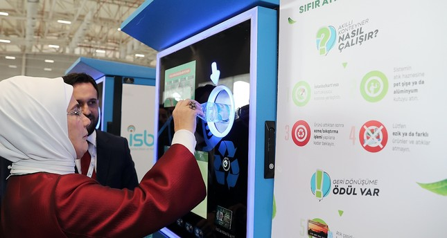 "First lady Emine Erdoğan deposits a plastic bottle to a ""smart waste transfer machine"" that gives mass transit credits in exchange for plastic bottles during an event on the environment in Istanbul in December."