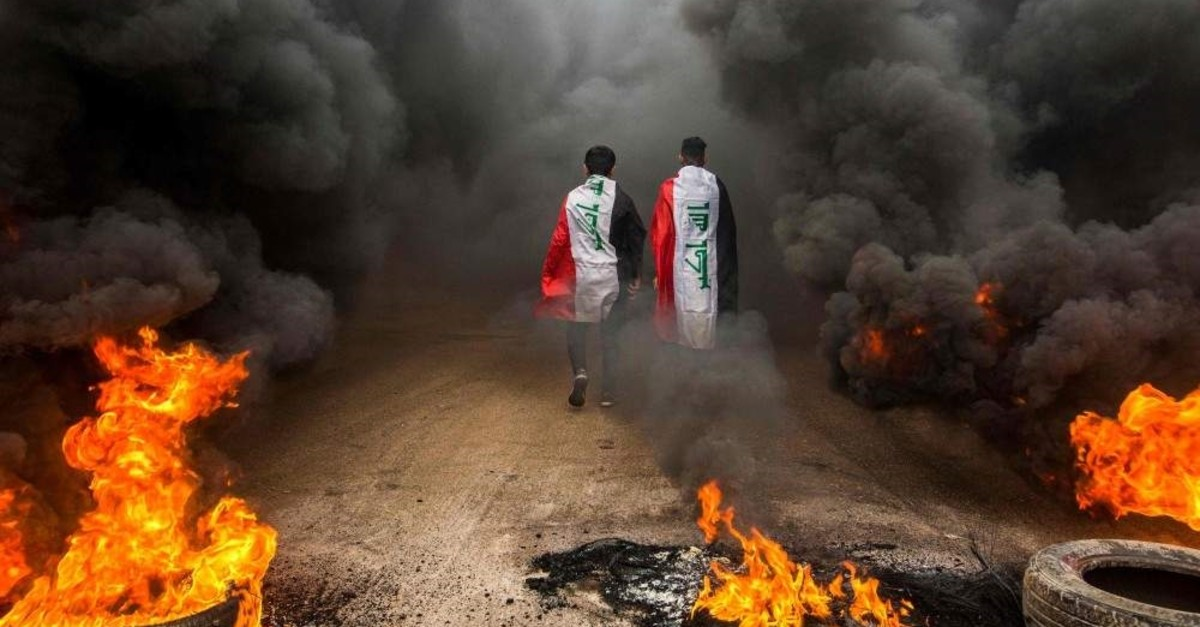 Anti-govt protesters draped in Iraqi national flags walk into clouds of smoke from burning tires during a demonstration in Basra on Nov. 17, 2019 (AFP Photo)