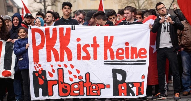 People hold a banner reading the PKK is not a worker's party during the Peace March for Turkey, organized by the new German Turkish Committee on April 10, 2016, in Nuremberg.