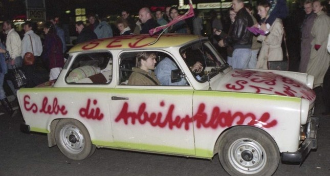 In this Nov. 11, 1989, file photo a Trabant car, made in East Germany, with a graffiti slogan 'Es lebe die Arbeiterklasse' (Shall the laboring classes live on) is pictured driving in West Berlin (AP File Photo)