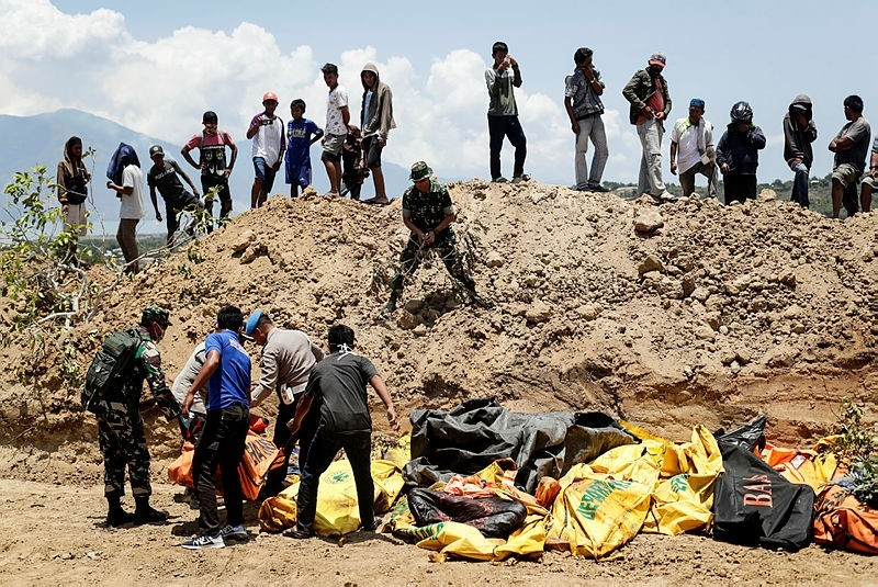Indonesian rescuers carry a body bag of a disaster victim during a mass burial at a field in Palu, central Sulawesi, Indonesia, 01 October 2018. (IHA Photo)