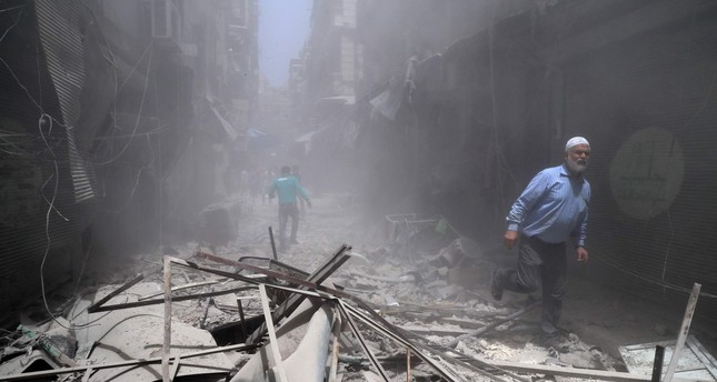Syrians walk through the rubble following a reported air strike by Syrian regime forces in the opposition-held neighbourhood of Bustan al-Qasr on June 5, 2016. (AFP PHOTO)