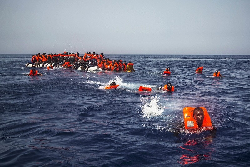 African migrants try to reach a rescue boat from the Spanish aid organization Proactiva Open Arms, after falling from a punctured rubber boat in the Mediterranean Sea, about 12 miles north of Sabratha, Libya, on July 23, 2017. (AP Photo)