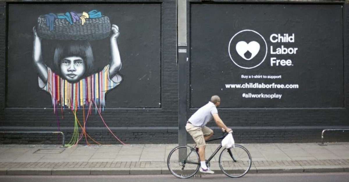 A cyclist passes a mural created by street artists for Child Labor Free, a social enterprise that accredits consumer brands that do not use child labour in their products, east London, 8 June 2016. (Reuters / Shanshan Chen)