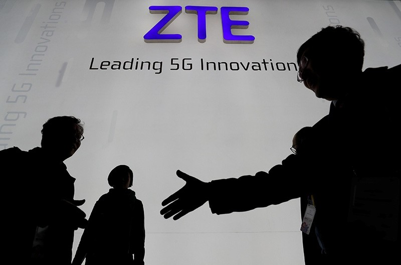 Visitors pass in front of the Chinese telecoms equipment group ZTE Corp booth at the Mobile World Congress in Barcelona, Spain, Feb. 26, 2018. (Reuters Photo)
